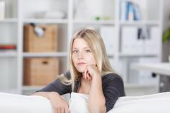 Woman with hand on chin sitting on sofa Stock Photos