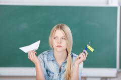 Female student holding paperboat and flag against chalkboard Stock Photos