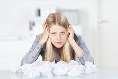 Businesswoman with heap of wastepaper on desk Stock Photos
