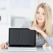 businesswoman displaying laptop at office desk - stock photo