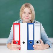 Female student with colorful binders at desk in classroom Stock Photos