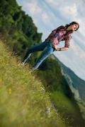 Stock Photo of beautiful woman in jeans standing on the grass