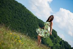 young woman in dress standing on the grass - stock photo