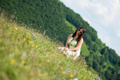 young woman in dress sitting on the grass - stock photo