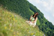 Stock Photo of young woman in dress sitting on the grass