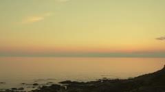 Women walking along coast during sunset Stock Footage
