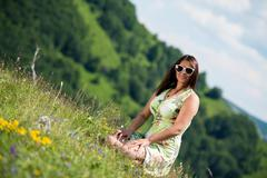 Young woman in dress sitting on the grass Stock Photos