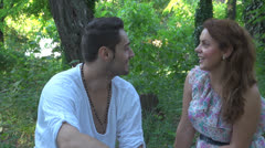 Two lovers sitting on the grass, talking. laughing Stock Footage