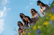 Stock Photo of group of girls sitting on grass and having fun