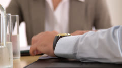 Businessman checking his watch in a meeting Stock Footage
