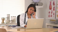 Japanese doctor talking on the phone in the office Stock Footage