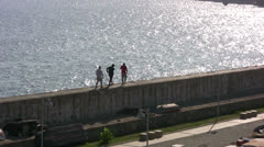 People walking along top of harbor wall at Kaleici harbor Stock Footage