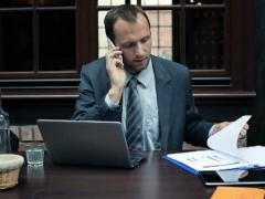 Businessman with laptop and documents talking on cellphone NTSC Stock Footage