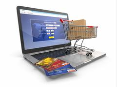 Stock Illustration of e-commerce. shopping cart and credit cards on laptop. 3d