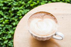 Free pour hot coffee latte serving on wood table Stock Photos
