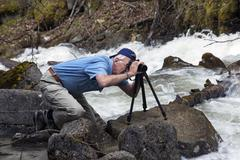 Photographer by Alaskan waterfall river - stock photo