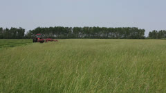 Cutting Hay in large field Stock Footage