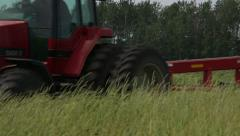 Cutting Hay tractor moves right to left through shot Stock Footage