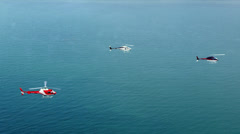 Aerial of 3 private helicopter flying in formation Stock Footage