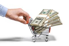 businessman's hand & steel grocery cart full of money stacks - isolated on white - stock photo