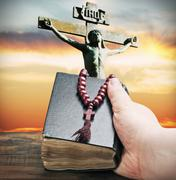 Hand holds the bible on the background of the crucifixion of jesus chris Stock Photos