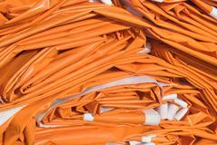 folded tarpaulin in orange - stock photo