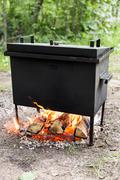 mobile camp smokehouse warm on wood and fire - stock photo
