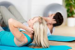 Couple doing sit ups on exercise mat Stock Photos