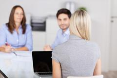 businesswoman with colleagues in meeting at conference desk - stock photo