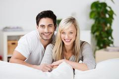 Mid adult couple at sofa in house Stock Photos