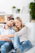 couple with eyes closed relaxing on sofa - stock photo