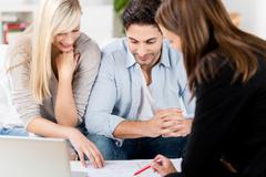 Financial advisor explaining document to couple at table Stock Photos