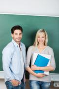 teachers standing against chalkboard in classroom - stock photo