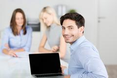 Stock Photo of businessman smiling with colleagues in background at desk