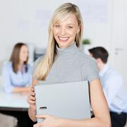 businesswoman holding binder with coworkers in background - stock photo