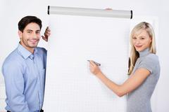 businesswoman writing on flipchart - stock photo