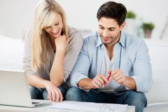 couple with laptop looking at document on table - stock photo