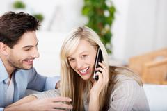 woman conversing on cordless phone while man looking at her - stock photo