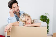 Tired couple leaning on cardboard box Stock Photos