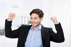 Businessman with arms raised celebrating victory Stock Photos