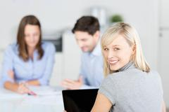 businesswoman looking over shoulder with colleagues discussing i - stock photo