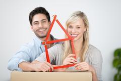 Couple holding ruler house on cardboard box Stock Photos