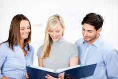 Business colleagues reading a folder Stock Photos