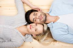 affectionate young couple lying head to head - stock photo