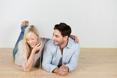 Laughing young couple lying on the floor Stock Photos
