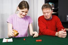 Girl and grandpa playing dice Stock Photos