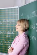 Student leaning against the blackboard Stock Photos
