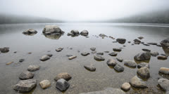 Fog rolling in over stones in a pond. Stock Footage