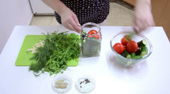 Packing cucumbers and tomatoes into sterilized jars - stock footage