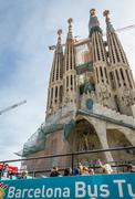 people in a turistic bus in front of the sagrada familia cathedral, designed - stock photo
